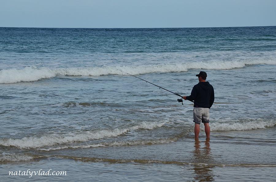 Рыбалка в Австралии Рыбак на пляже с удочкой