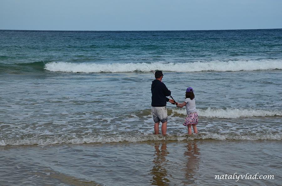 Рыбаки папа и дочь на берегу океана